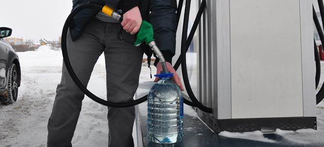наливает бензин в пластиковую канистру на заправке